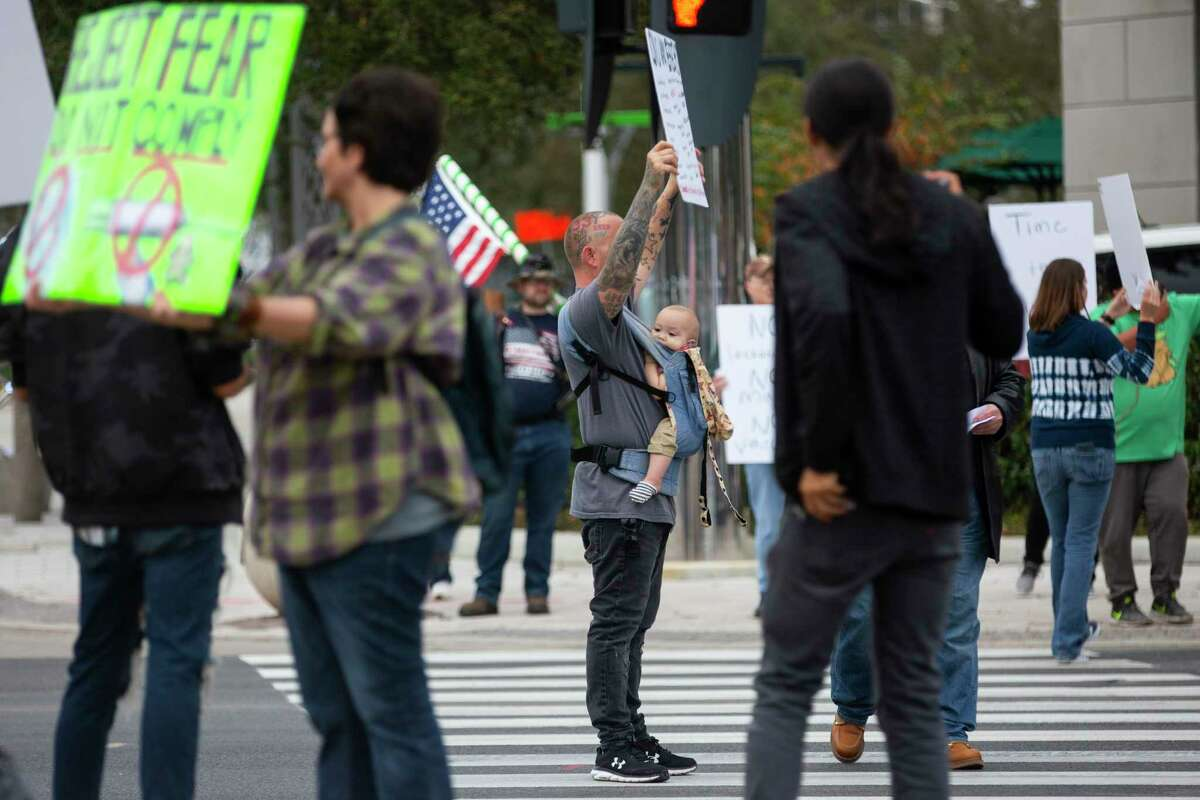 Justin Bond joins other protestors at the intersection of Westheimer and Post Oak Blvd. during the Rally for Covid-19 Liberty, Health, and Choice on Saturday, Dec. 12, 2020.