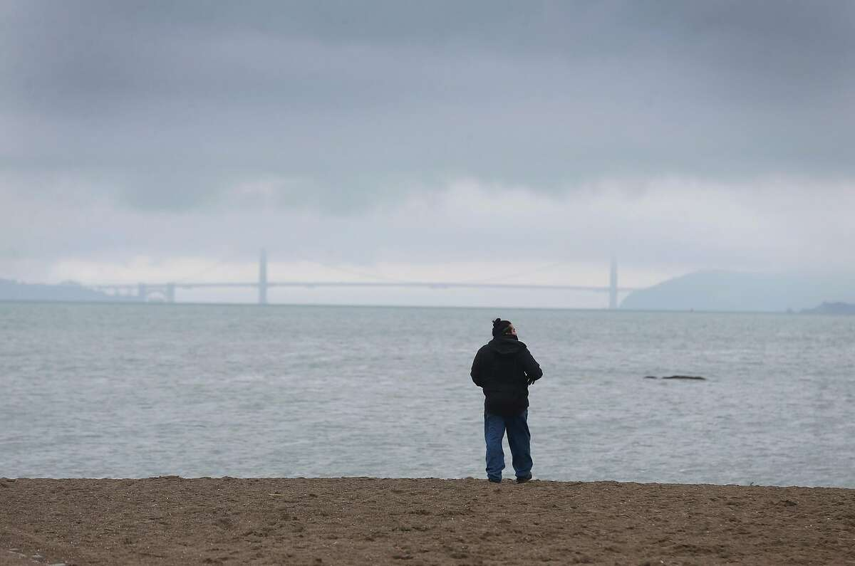 A man feels the cool breeze during a break between weekend rainstorms at Albany Beach in Albany.