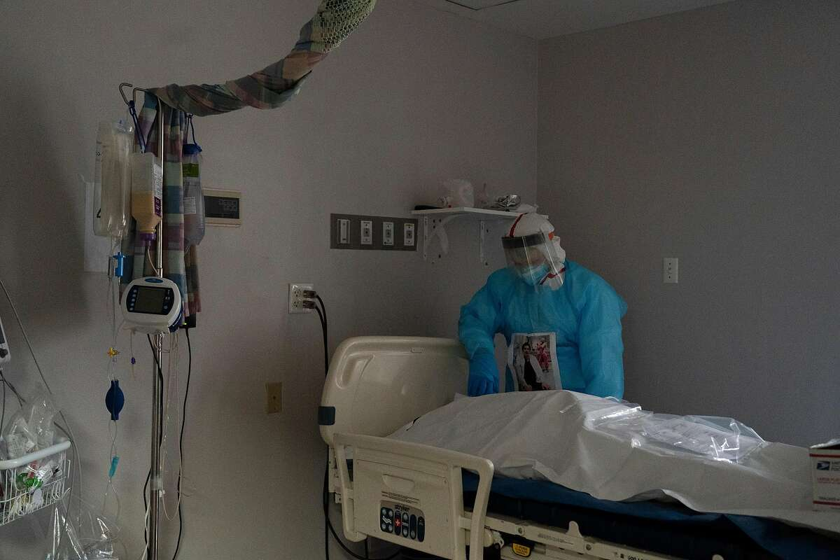 A medical worker stands and takes a moment by a deceased patient wrapped in a body bag in the COVID-19 intensive care unit at a hospital in Houston. Texas has the second-highest death toll in the country, behind New York.