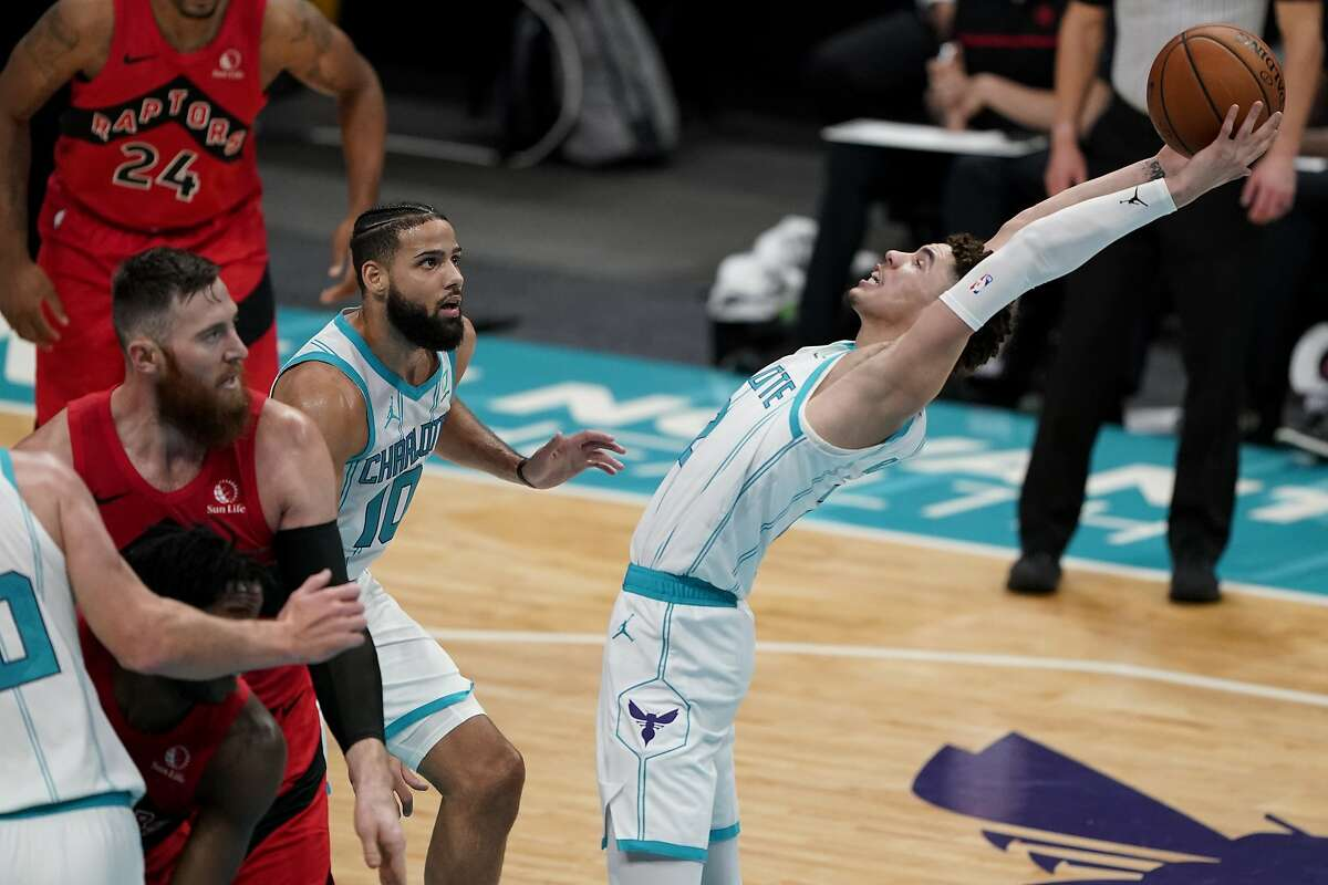 Hornets guard LaMelo Ball grabs one of his 10 rebounds in his first time on an NBA court, an exhibition against Toronto.