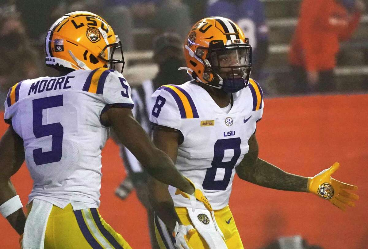 LSU running back Tre Bradford (8) is congratulated by wide receiver Koy Moore (5) after Bradford scored a touchdown during the second half of the team's NCAA college football game against Florida, Saturday, Dec. 12, 2020, in Gainesville, Fla.