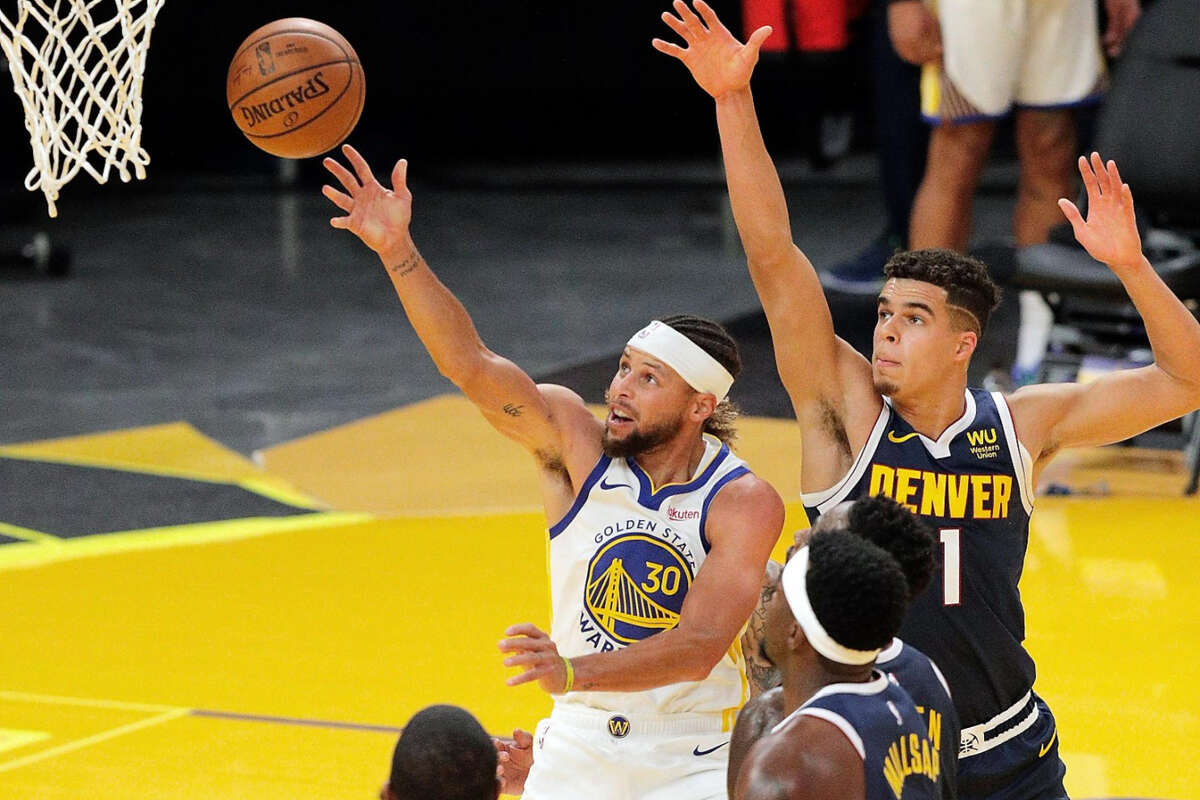 Stephen Curry (30) puts up a shot during the first half as the Golden State Warriors played the Denver Nuggets in their first preseason game at Chase Arena in San Francisco, Calif., on Saturday, December 12, 2020.