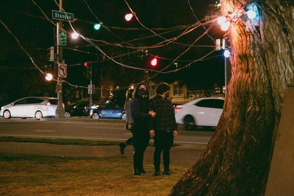 A masked couple take in the view of San Francisco's official Christmas tree at the entrance of Golden Gate Park on Thursday. Under San Francisco's revised health order, outdoor visits with one person outside your immediate household are now allowed.