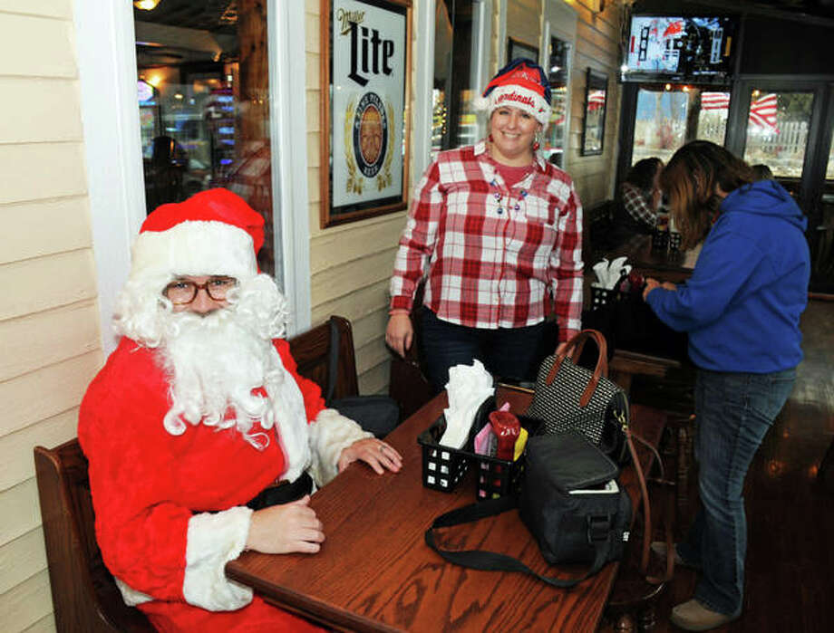 Dustin Treise, of Alton, waits for some refreshment while participating in Grafton's second annual SantaCon Saturday. Photo: David Blanchette|For The Telegraph