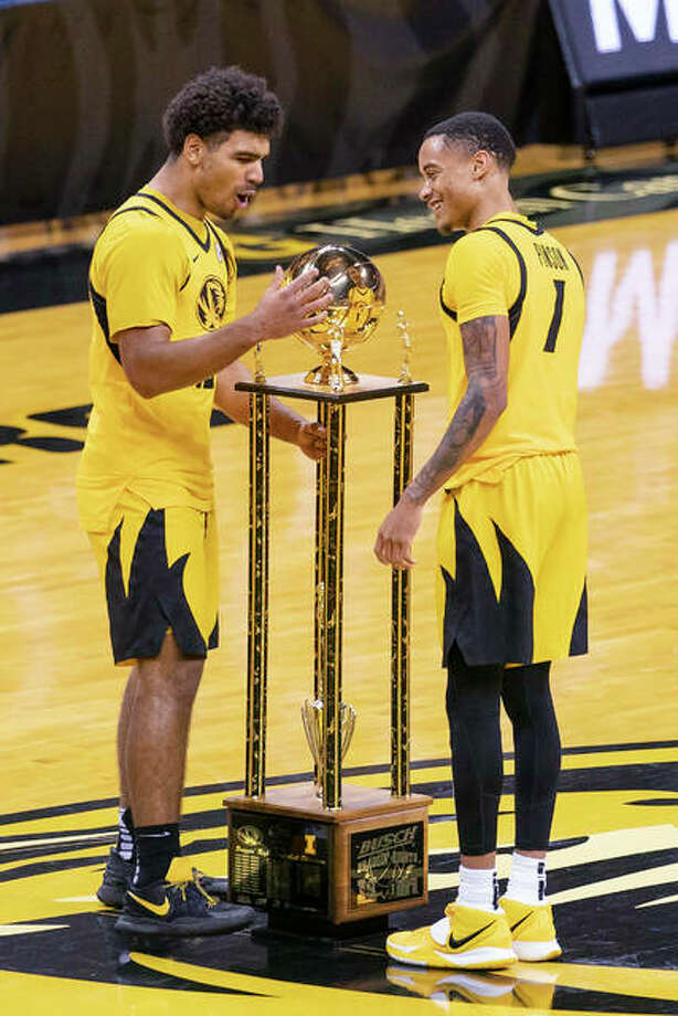 Missouri's Mark Smith, left, and Xavier Pinson admire the Braggin' Rights trophy on the court of Mizzou Arena after they defeated Illinois 81-78 in an NCAA college basketball game Saturday, Dec. 12, 2020, in Columbia, Mo.