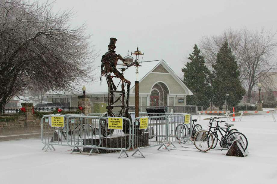 Snow falls around the Lamplighter sculpture in downtown Manistee on Saturday. (Michelle Graves/News Advocate)