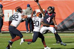 Houston Texans quarterback Deshaun Watson (4) throws the ball away as he is chased out of the pocket by Chicago Bears defensive end Brent Urban (92) and cornerback Duke Shelley (20) during the first quarter of an NFL football game at Soldier Field Sunday, Dec. 13, 2020, in Chicago.