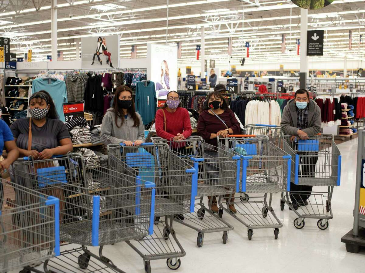 Families line up to participate in a Christmas shopping spree sponsored by Milas Williams' nonprofit World Lolei where each family was given $1,000 to use at Walmart on Saturday, Dec. 12, 2020, in San Antonio.