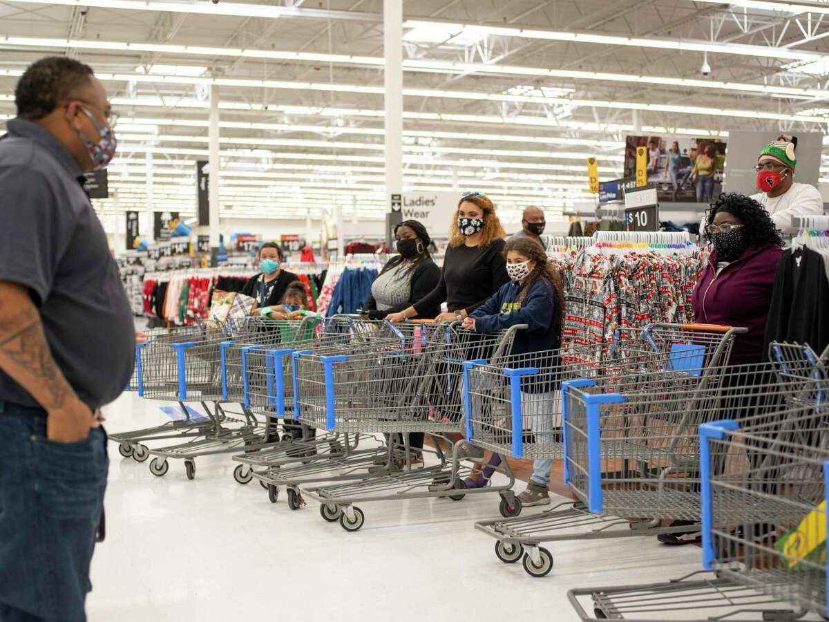Milas Williams, founder of the nonprofit World Lolei, left, speaks to 10 families who each received a $1,000 shopping spree at Walmart on Saturday, Dec. 12, 2020, in San Antonio.