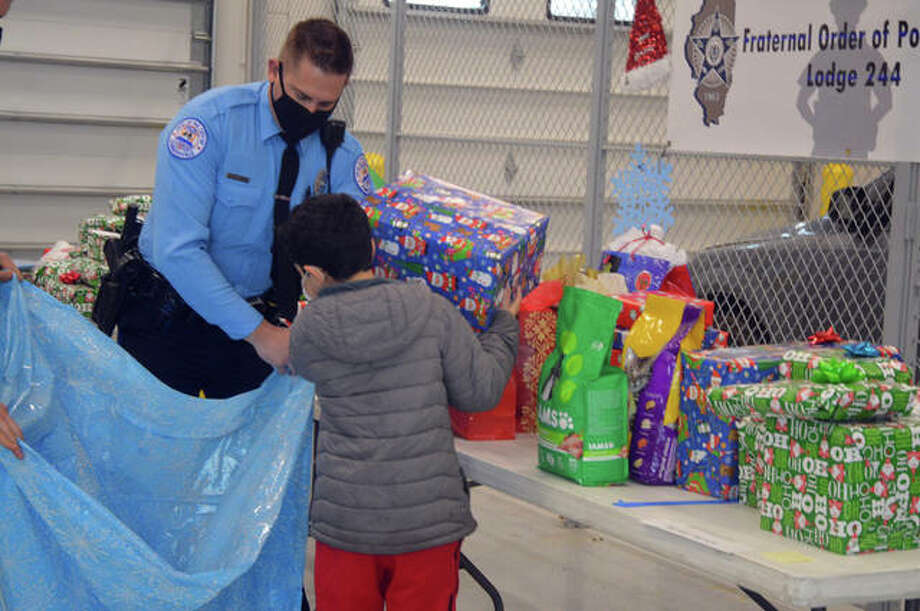 """Edwardsville Police Sergeant Matt Breihan distributes gifts to kids during Saturday's """"Christmas with a Cop"""" program at the Edwardsville Police Department. Photo: Scott Marion/For The Intelligencer"""