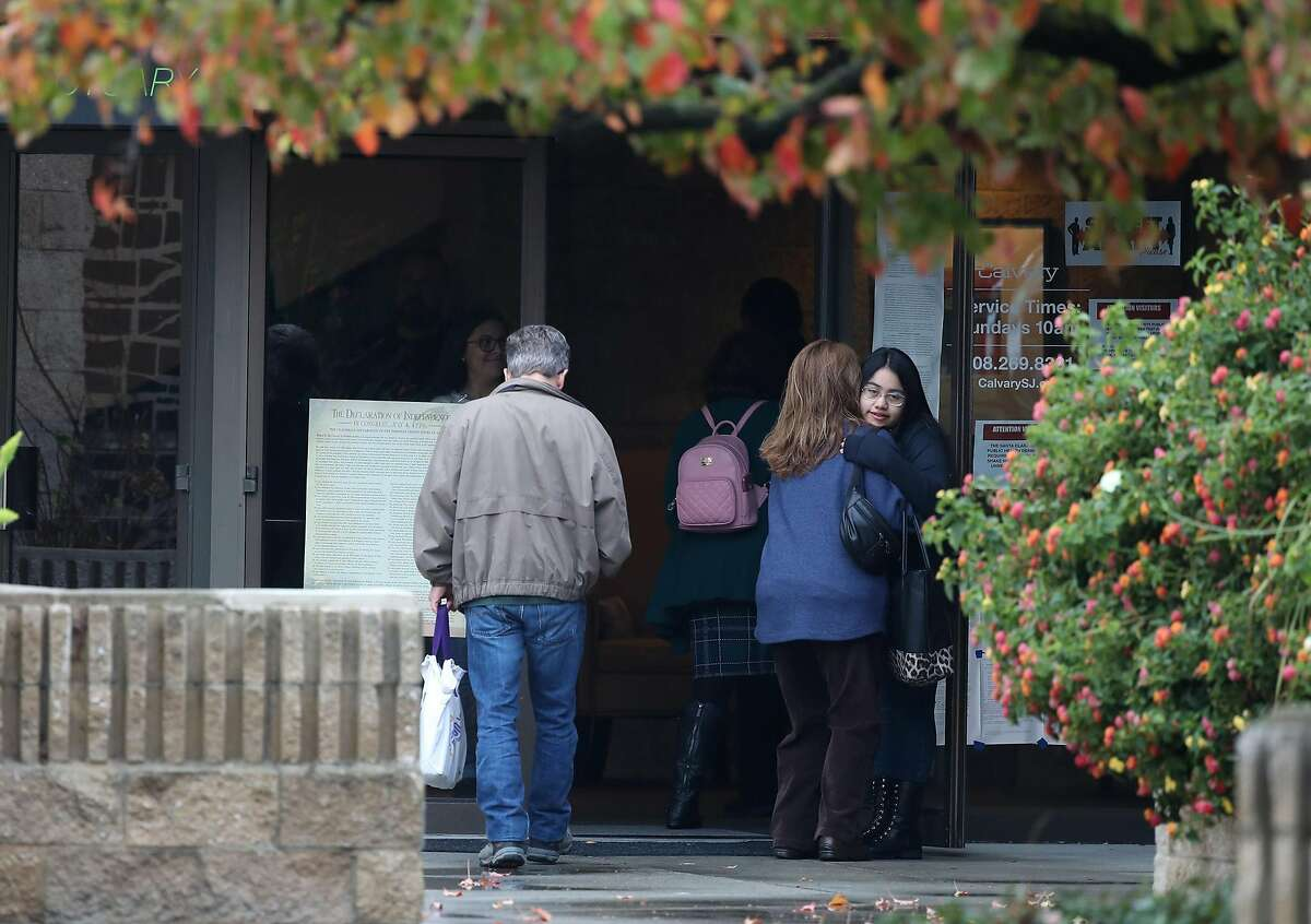 Attendees hug as they enter the service at the Calvary Chapel in San Jose, California on Sunday, December 13, 2020. Calvary Chapel, which has been found in contempt of court and fined for continuing to hold indoor services despite the lockdown in Santa Clara County, which only allows worship outside.
