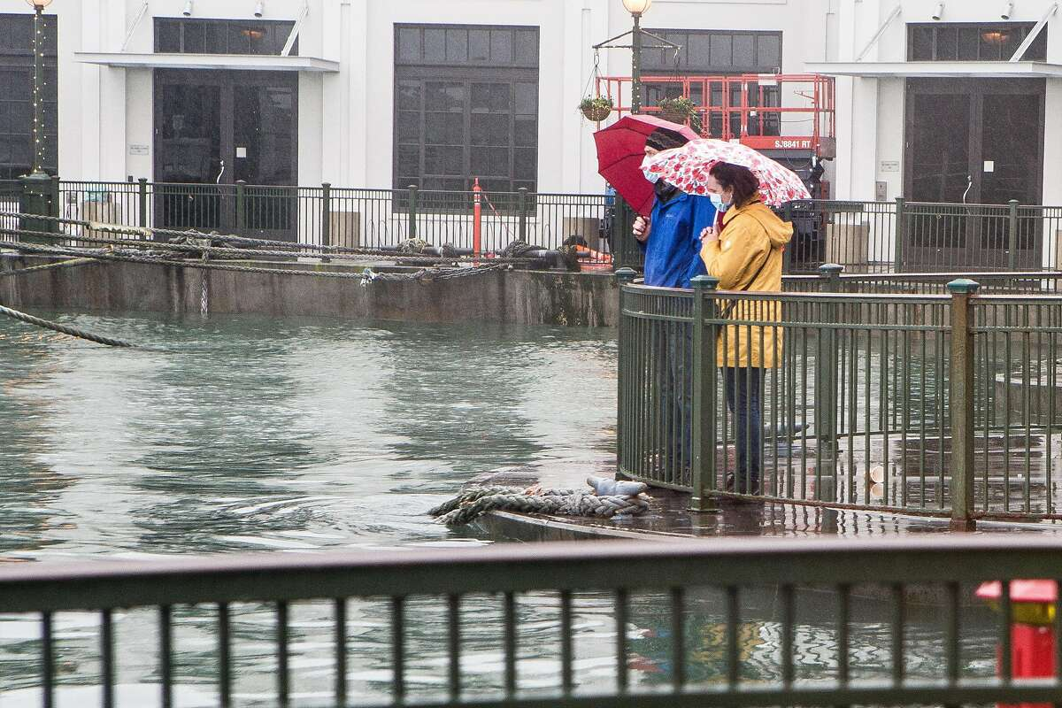 Marshall Chase and Julie Mueller brave the rain to check out the high water level during a king tide event on Sunday.