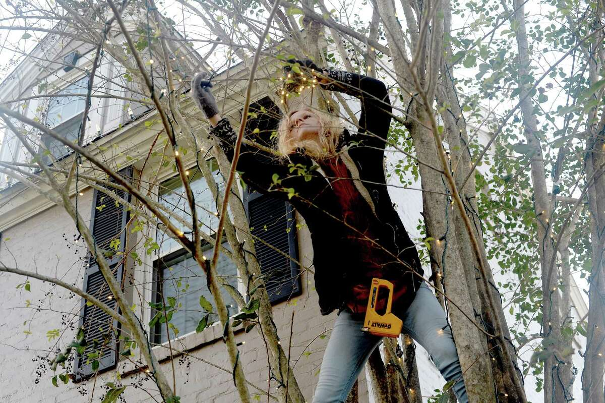 Shelby Welch balances amid the branches of a crepe myrtle tree as she and co-worker Donna Middlebrook decorate outside a home inn the Calder Place neighborhood in Beaumont Friday evening. Welch and Middlebrook decorate as many as 4 homes a day, with deocratuve requests up this year compared to years past. Photo taken Friday, December 4, 2020 Kim Brent/The Enterprise