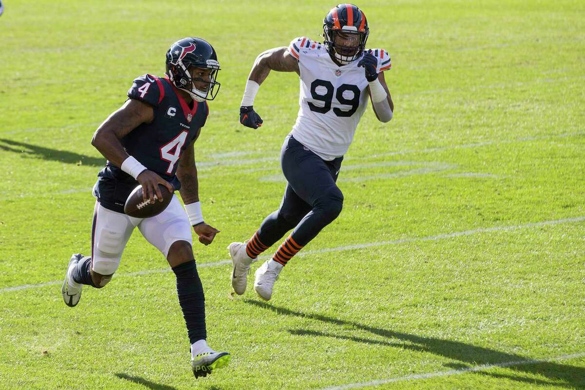 Houston Texans quarterback Deshaun Watson (4) runs downfield after being forced out of the pocket by Chicago Bears linebacker Trevis Gipson (99) during the first half of an NFL football game at Soldier Field Sunday, Dec. 13, 2020, in Chicago.