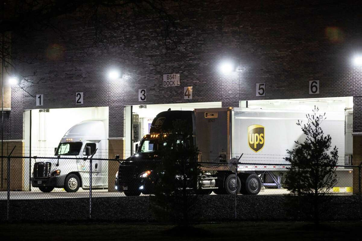 A FedEx and a UPS truck back into the loading dock at Pfizer Global Supply in Portage, Mich. on Dec. 13, 2020.