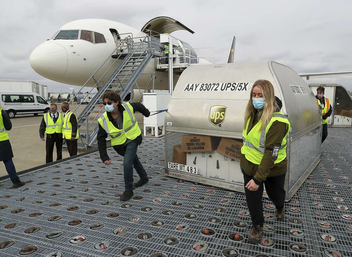 LOUISVILLE, KY - DECEMBER 13: UPS employees move one of two shipping containers containing the first shipments of the Pfizer and BioNTech COVID-19 vaccine a ramp at UPS Worldport in Louisville, Kentucky, on December 13, 2020. The flight originated in Lansing, Michigan. (Photo by Michael Clevenger - Pool/Getty Images)