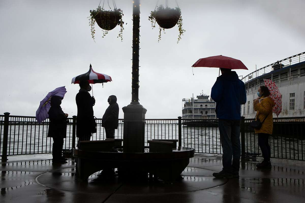 Marilynn Fowler (left), Claudia Miller, and Elise Everett admire the roiling water during Sunday's king tide.