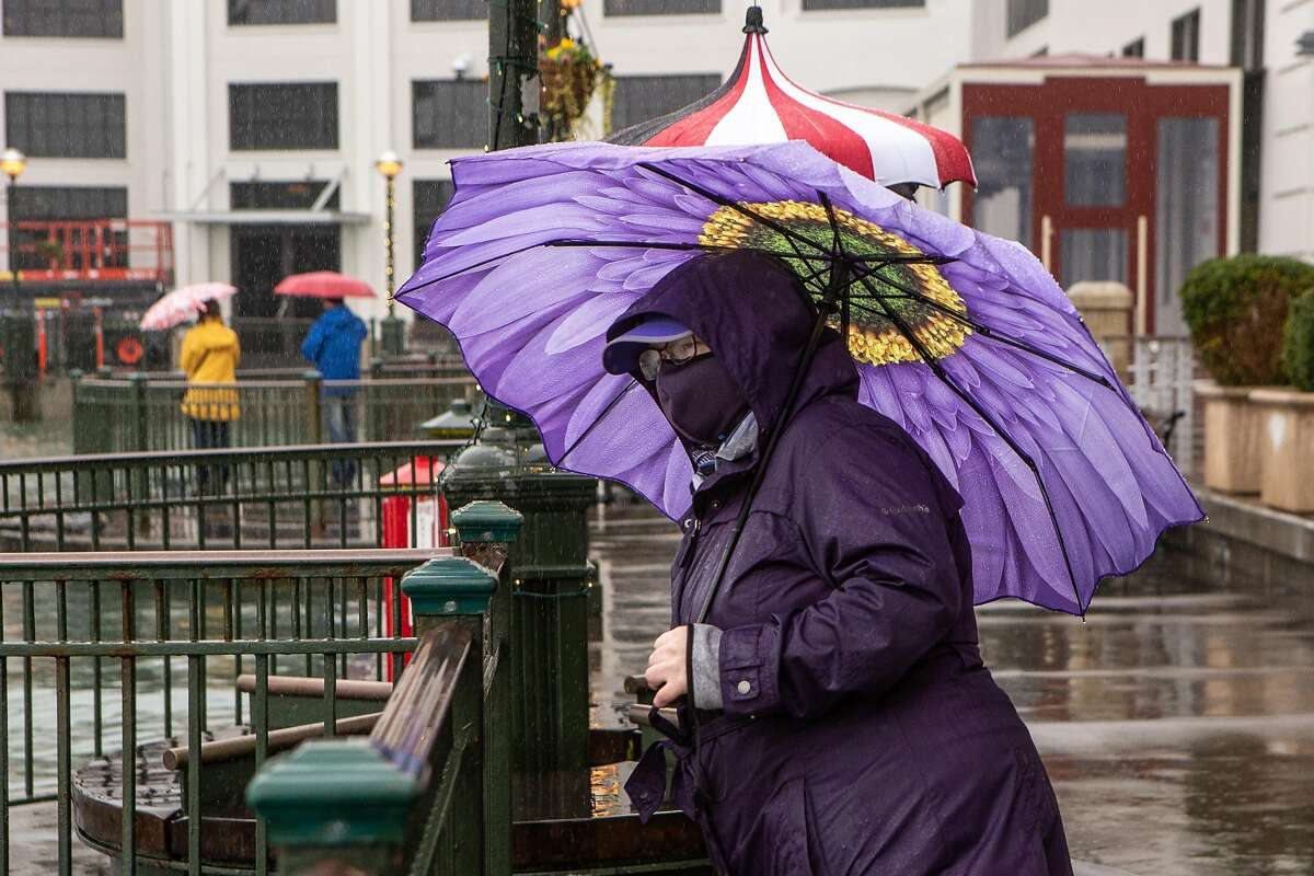 Elise Everett braves the rain on Sunday, December 13, 2020 in San Francisco, Calif. The Bay Area anticipates renewed showers ahead of the weekend.