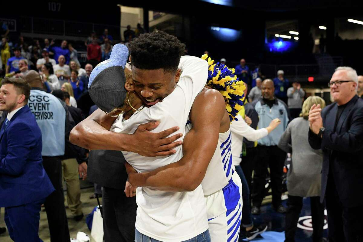 Hofstra guard Eli Pemberton, right, hugs a fan after the 2020 Colonial Athletic Association men's tournament in March.