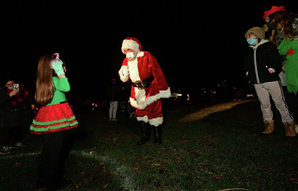 Santa, aka Joseph Hofflinger greets Emmy Tehrieiro, 5, as Celebrate Shelton holds its seventh annual community tree lighting Friday, December 11, 2020, at the Rotary Pavilion at Veteran's Memorial Park in Shelton, Conn. In addition to the tree lighting and the visit from Santa and Mrs. Claus, the event featured an ice sculpture demonstration by Ice Matters; a fire dance performance with Sarotonin Performance Arts; and a holiday dance party. The community tree lighting was sponsored by the city, Center Stage Theatre, Apple Rehab, Jones Family Farm, Echo Hose Hook & Ladder Co. 1 and Valley Community Foundation.