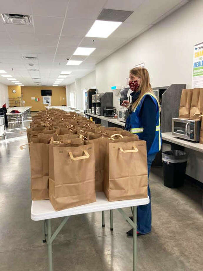 During the Thanksgiving season, an employee at Mother's Catering, in Highland, helps organize meals for delivery. For Christmas, the firm will help seniors in a partnership with Madison County.