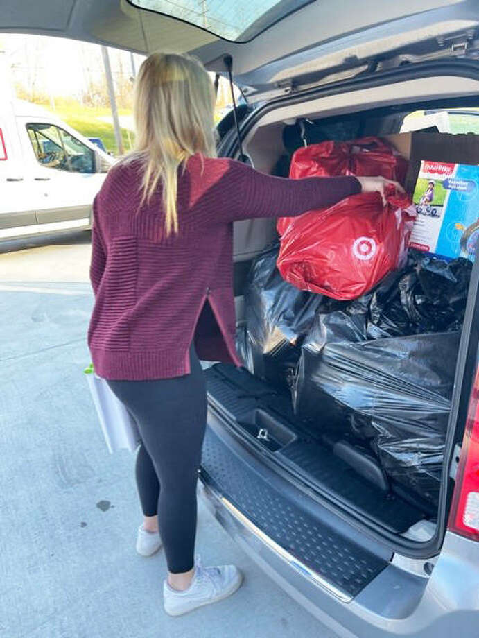 Taylor Freer loads a sport utility vehicle with items that the Freer Auto Body family purchased with their own money throughout the year to donate to the effort of Community Christmas. This year the United Way promoted a contactless annual Community Christmas, so the Freer sisters organized a way for nonprofits to pick up the items on their own so that families in need could receive the gifts and make their Christmas brighter. Photo: For The Telegraph