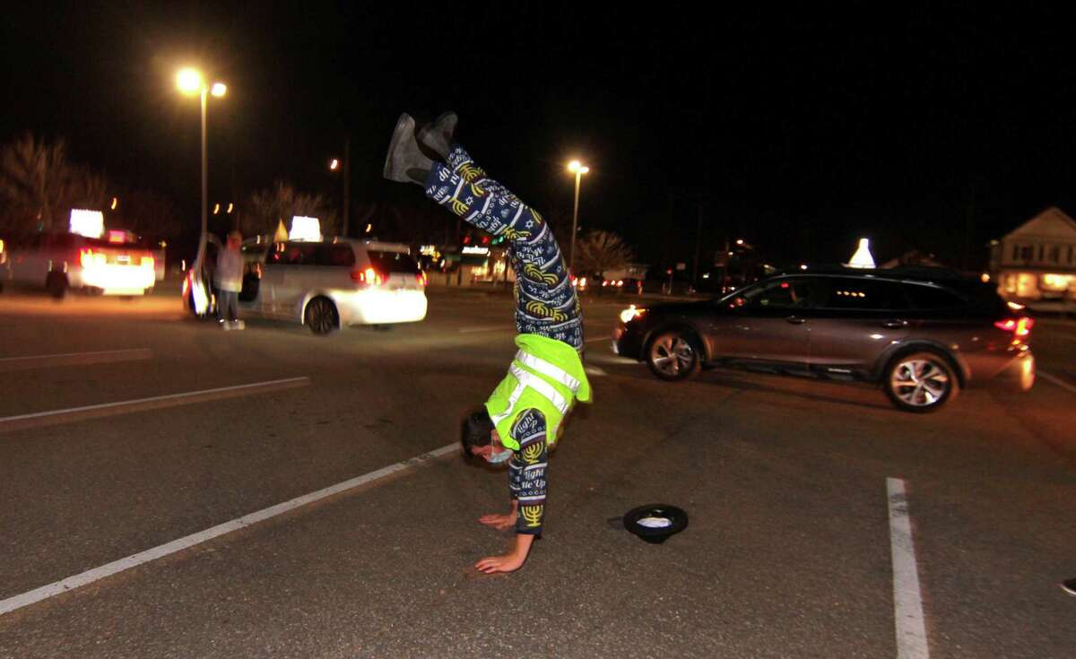 A members of Chabad of Fairfield does a handstand while dancing during a pause in a Car Menorah Parade along Post Road in Fairfield, Conn., on Thursday Dec. 10, 2020. A Menorah lighting to celebrate Hanukkah came at the end of the parade that started at Chabad of Fairfield, joined Chabad of Shelton and Chabad of Westport members midway along the route along Post Road in Fairfield.
