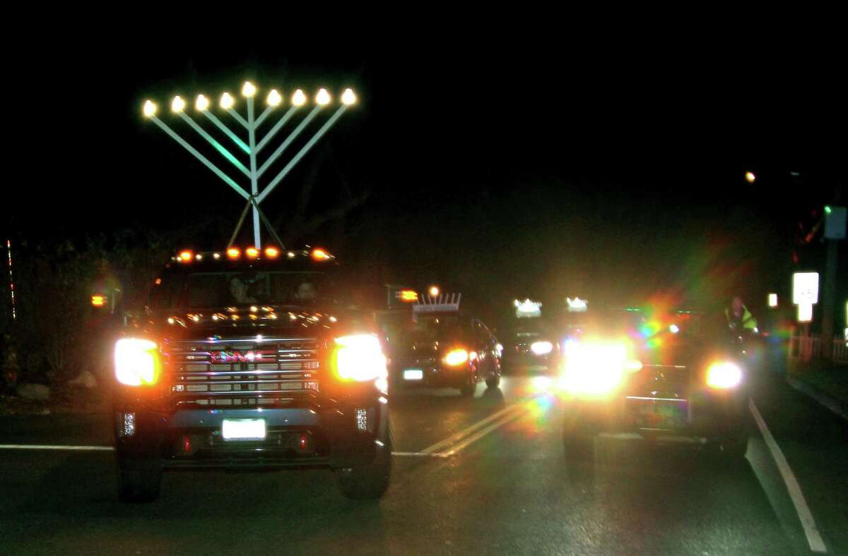 The lead vehicle in a Car Menorah Parade originating in Fairfield makes its way to the entrance to Chabad of Westport on Thursday. A Menorah lighting came at the end of the parade that started at Chabad of Fairfield, joined Chabad of Shelton and Chabad of Westport members midway along the route along Post Road in Fairfield. See more photos on page A6.