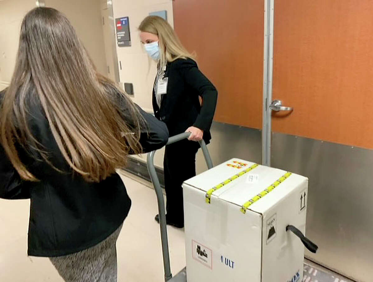 Shipment of Pfizer's COVID-19 vaccine is taken from FedEx truck to MD Anderson Cancer Center's pharmacy Monday morning.