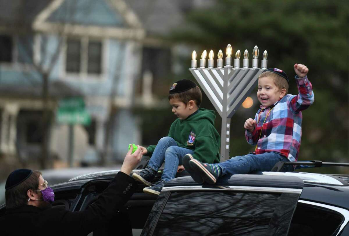Above, Yossi Kamman and his children Levi, 3, and Mendel, 5, prepare for the at Perrot Memorial Library in Old Greenwich, Conn. Sunday, Dec. 13, 2020. Participants assembled at the library and were escorted through Greenwich to the Chabad giant menorah on Greenwich Avenue.