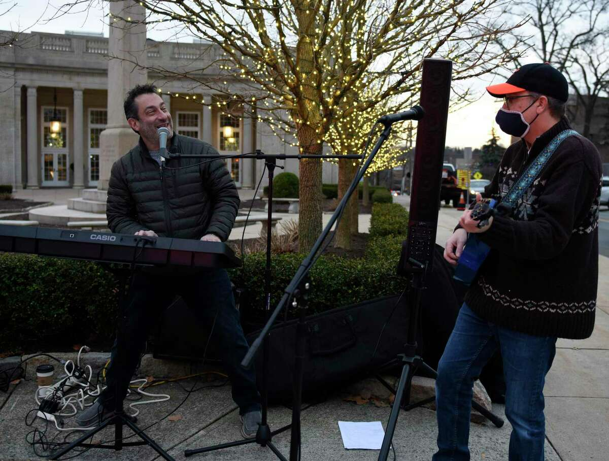 Jonathan Carr, left, and Bobby Doowah perform Hanukkah songs at the Chabad giant menorah in Greenwich, Conn. Sunday, Dec. 13, 2020. Folks celebrated Hanukkah by having a car parader through Greenwich to the Chabad giant menorah on Greenwich Avenue.