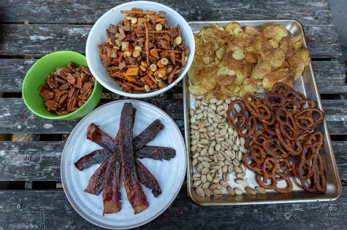A selection of smoked holiday snacks include (clockwise from top left) Smoked and Spiced Pecans, Smoked Sweet and Spicy Chex Party Mix, potato chips, pretzels, pistachios and Smoked Pig Candy sweet bacon.