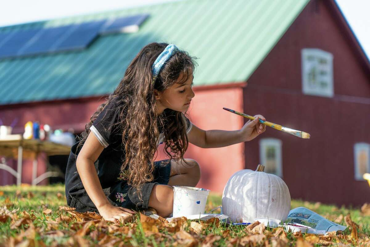 3rd Grader Sophie Sax, sitting six feet away from the other participants, paints her Dia De Los Muertos-inspired pumpkin at Waldingfield Farm on ASAP!'s A Day On The Farm Field Trip.