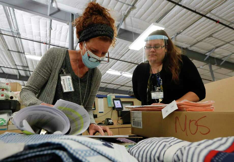 Brenda Price, right, helps sort through donated items along with Lisa Van De Walle, center, and Tana Garner at Habitat for Hummanity MCTX's ReStore thrift store, Wednesday, Dec. 9, 2020.. Price, who currently lives in a subsidized hosing, is working to complete the 350 'sweat equity' hours required as part of the non-profits housing program. She and her family are the first graduates of the Family Promise of Montgomery County's program for needy families to be accepted to the housing program. Photo: Jason Fochtman, Houston Chronicle / Staff Photographer / 2020 © Houston Chronicle