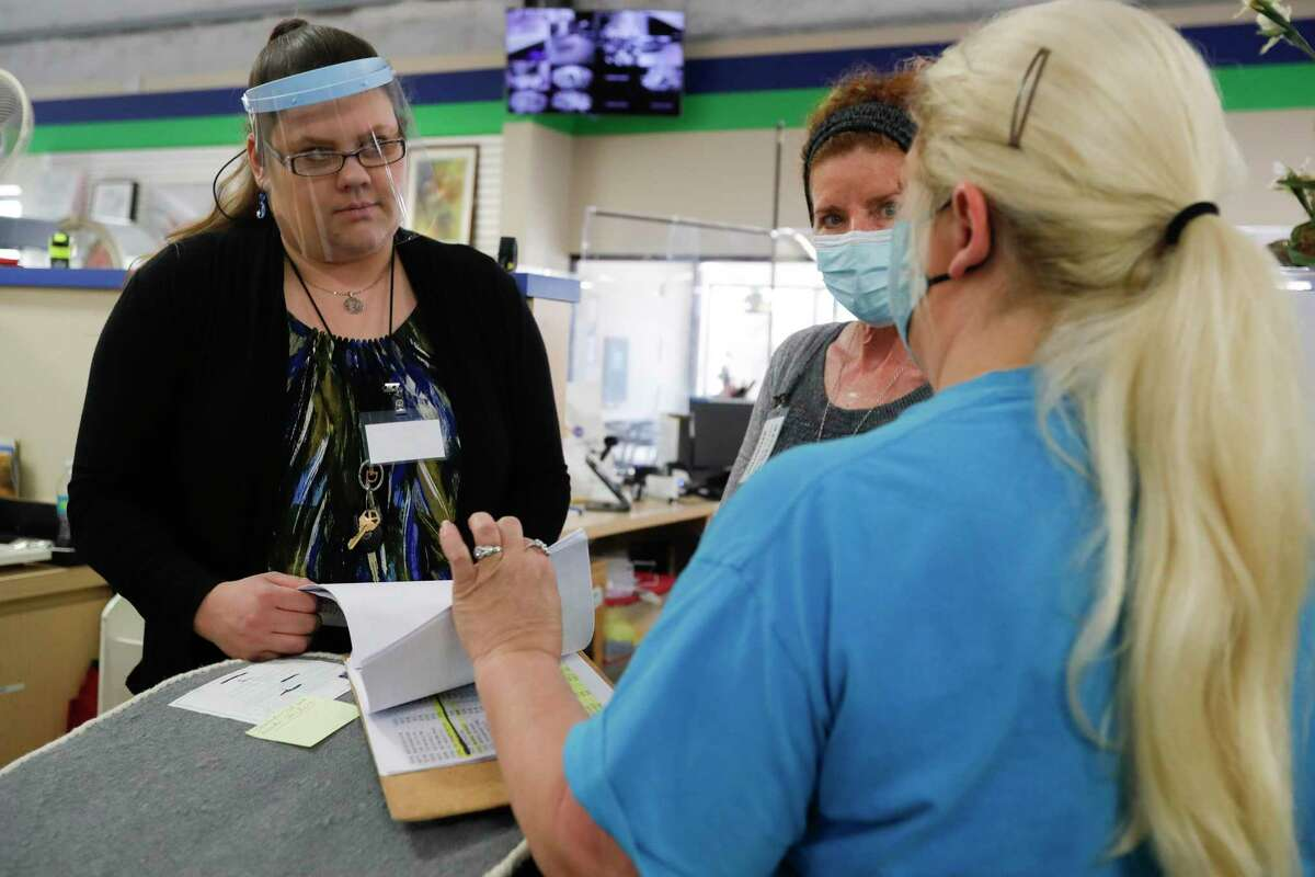 Brenda Price, left, listens to instructions for sorting and cataloging items at Habitat for Hummanity MCTX's ReStore thrift store, Wednesday, Dec. 9, 2020.. Price, who currently lives in a subsidized hosing, is working to complete the 350 'sweat equity' hours required as part of the non-profits housing program. She and her family are the first graduates of the Family Promise of Montgomery County's program for needy families to be accepted to the housing program.