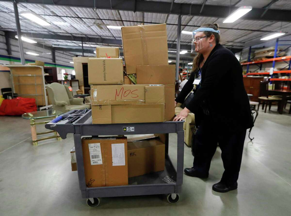 Brenda Price pushes several boxes of items to be sorted at Habitat for Hummanity MCTX's ReStore thrift store, Wednesday, Dec. 9, 2020.. Price, who currently lives in a subsidized hosing, is working to complete the 350 'sweat equity' hours required as part of the non-profits housing program. She and her family are the first graduates of the Family Promise of Montgomery County's program for needy families to be accepted to the housing program.
