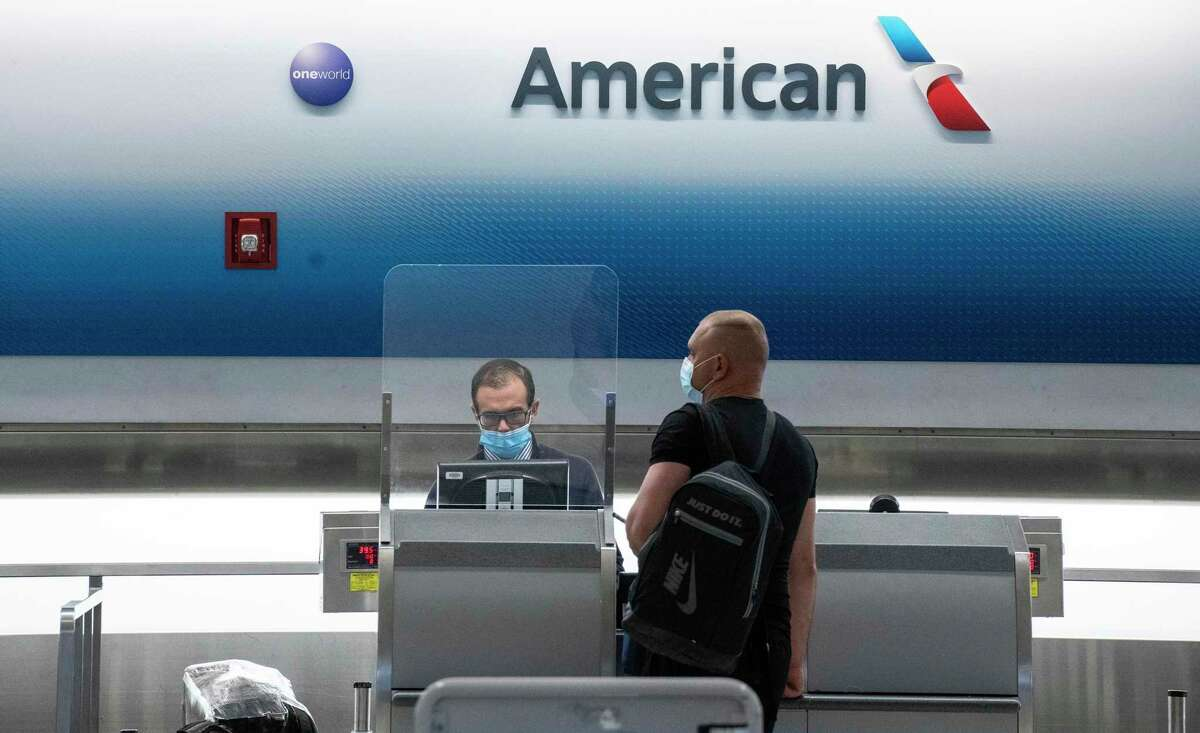An American Airlines employee assists a traveler at Miami International Airport. American was the first of the major carriers to announced they would stop charging fees for flight changes for nonrefundable international tickets.