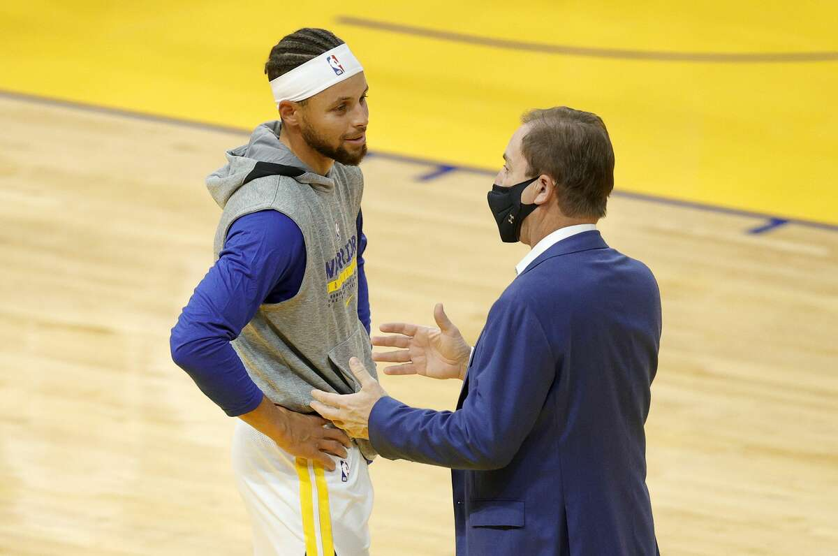Stephen Curry #30 of the Golden State Warriors talks to Warriors' owner Joe Lacob before their NBA preseason game against the Denver Nuggets at Chase Center on December 12, 2020 in San Francisco, California.