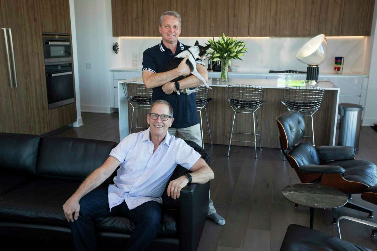 Tim Kollatschny, standing and holding their 15-year-old dog, Chloe, and Stephen Goldberg pose for a portrait in the living room of their condo at The Mond at The Museums.