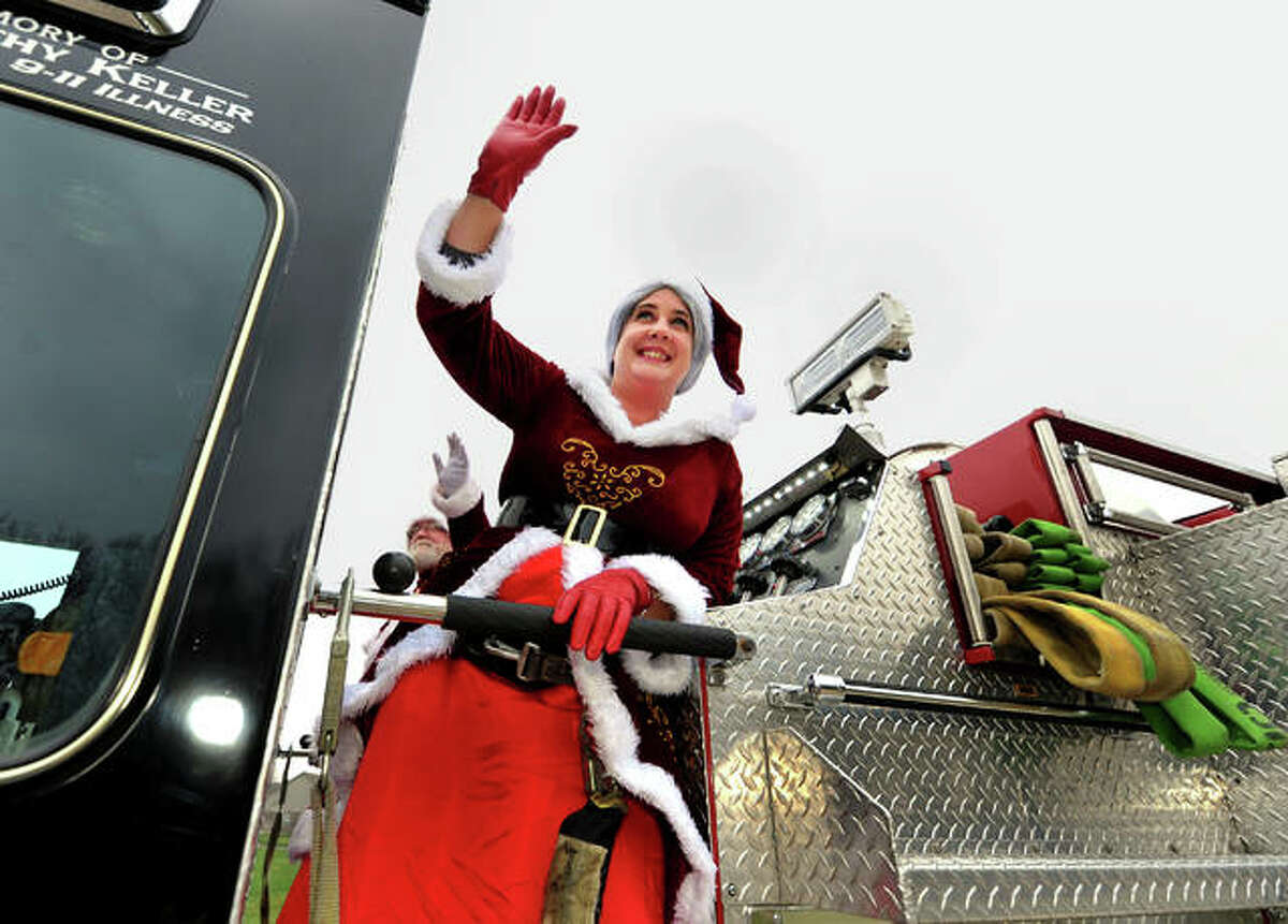 Mrs. Claus waves to families as she and Santa ride atop a Highland Fire Department truck and through the city's neighborhoods Sunday to spread some holiday cheer.