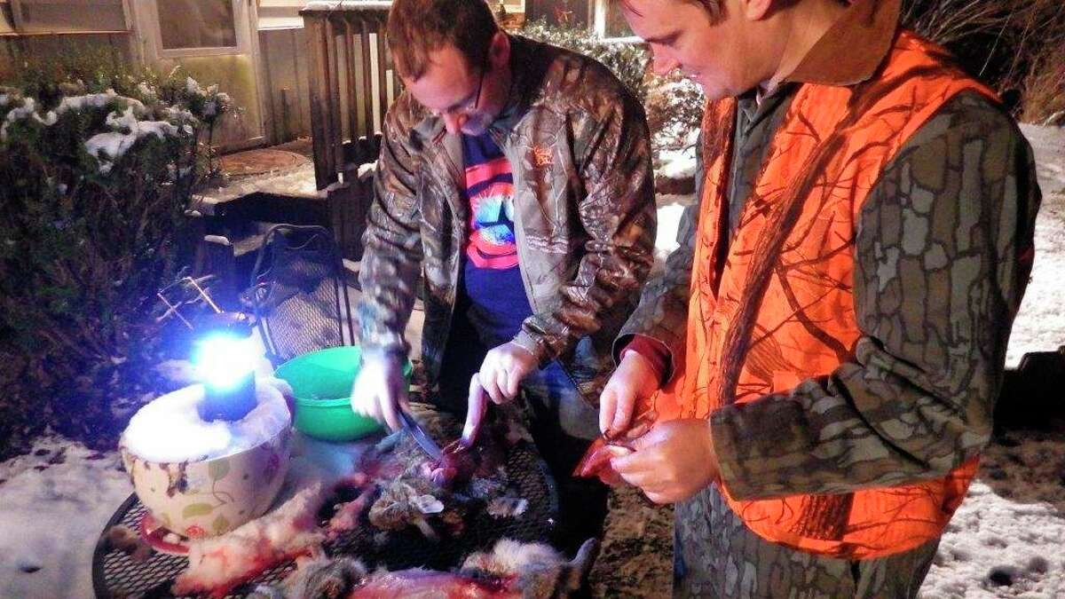 Jake Lounsbury (left) and Josh Lounsbury dress out freshly hunted rabbits. They are wearing rubber gloves to avoid poison ivy, and the work is being done outside to avoidbringing fleas into the home. (Tom Lounsbury/Hearst Michigan)