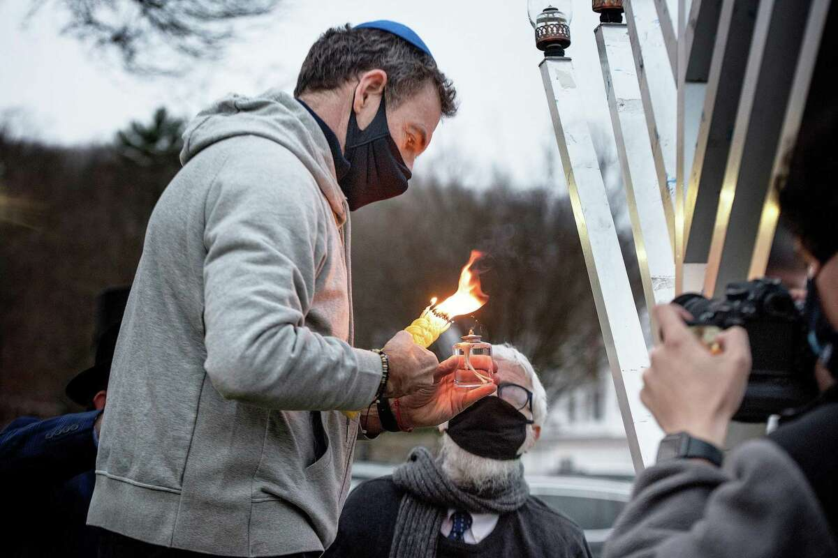 Rabbi Hecht of Beth Israel Synagogue Chabad in Norwalk helps John Reznikoff of Wilton light the menorah on the fourth night Hanukkah on Sunday, Dec. 13, 2020, at the Wilton Town Green.