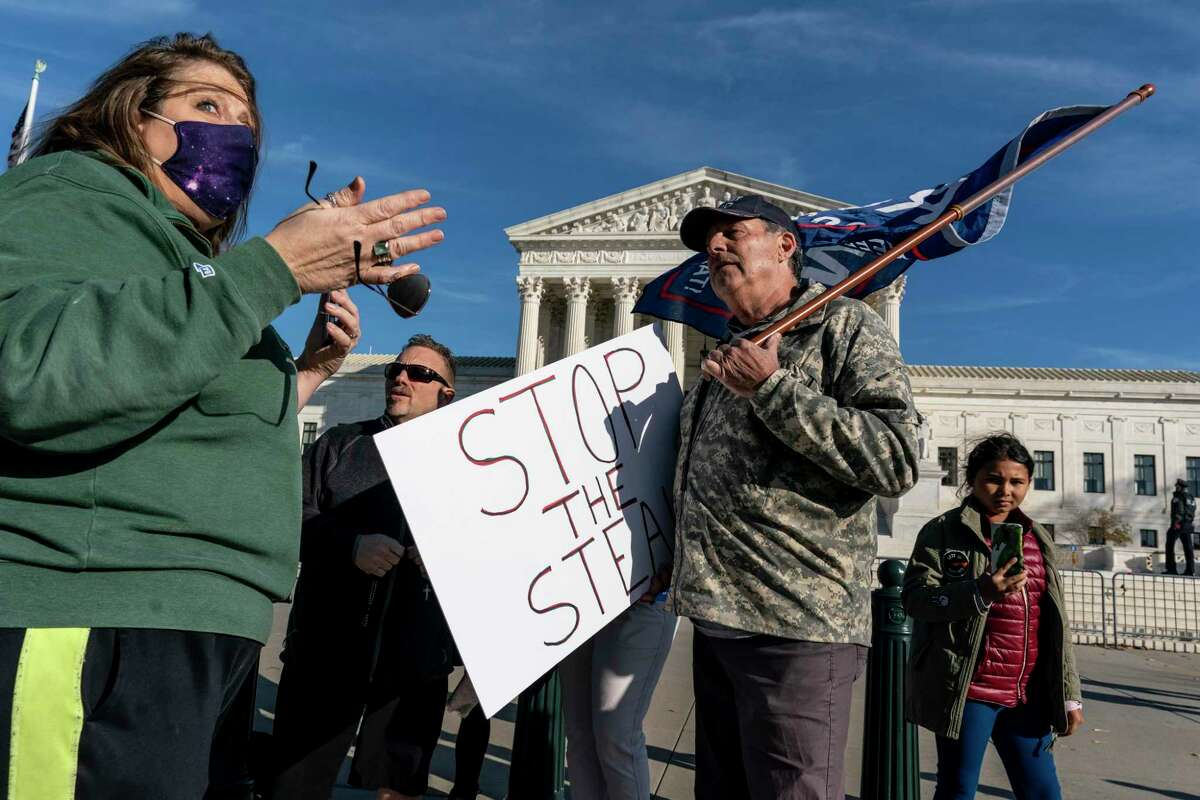 Activists debate President Donald Trump's claims of voter fraud outside the Suprme Court on Friday.
