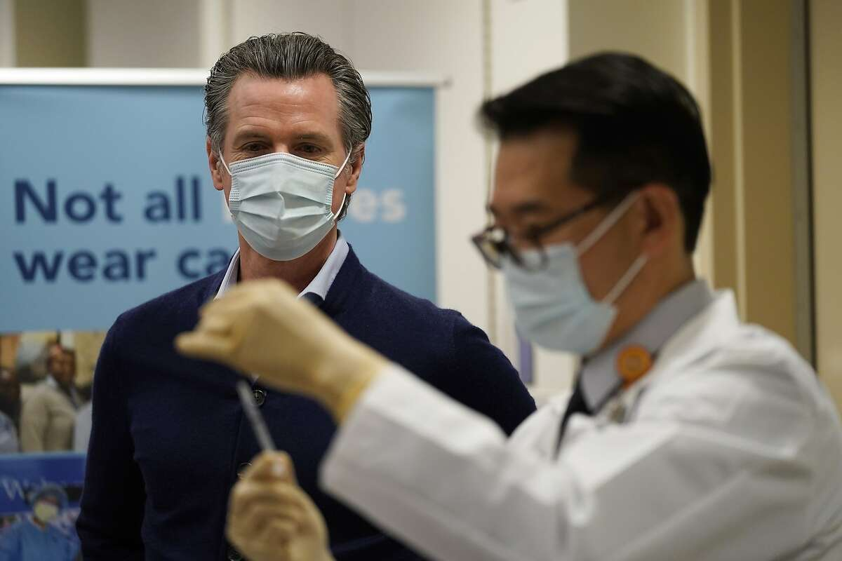 California Gov. Gavin Newsom watches as the Pfizer-BioNTech COVID-19 vaccine is prepared by Director of Inpatient Pharmacy David Cheng at Kaiser Permanente Los Angeles Medical Center in Los Angeles, Monday, Dec. 14, 2020. (AP Photo/Jae C. Hong)