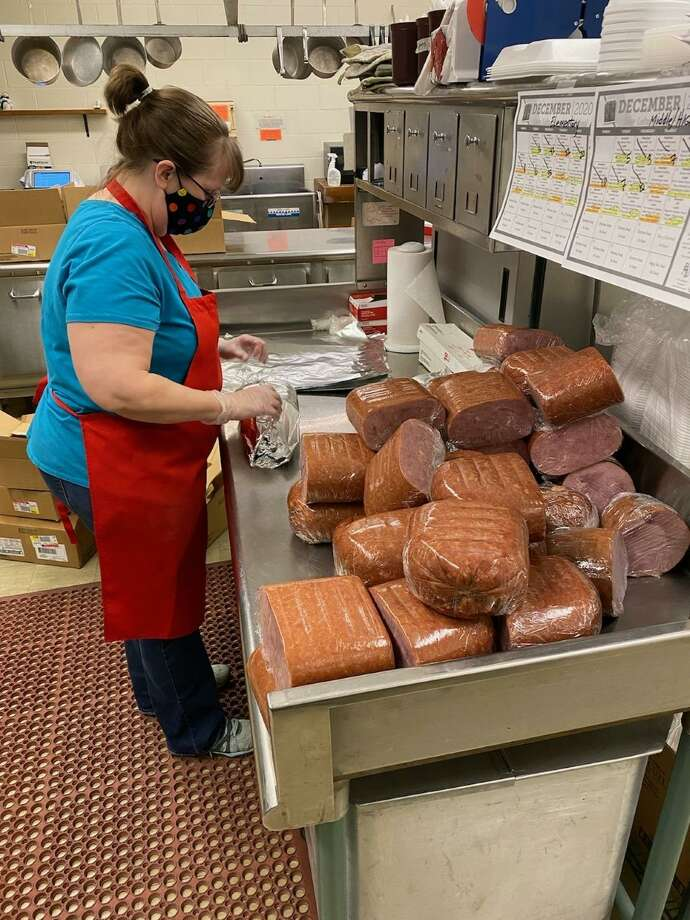 Fresh cut hams are prepared for Christmas meal kits at Kaleva Norman Dickson Schools on Monday. The special dinners will be included as part of the curbside pickups at KND, Bear Lake and Onekama Consolidated Schools on Thursday. Photo: Courtesy Photo