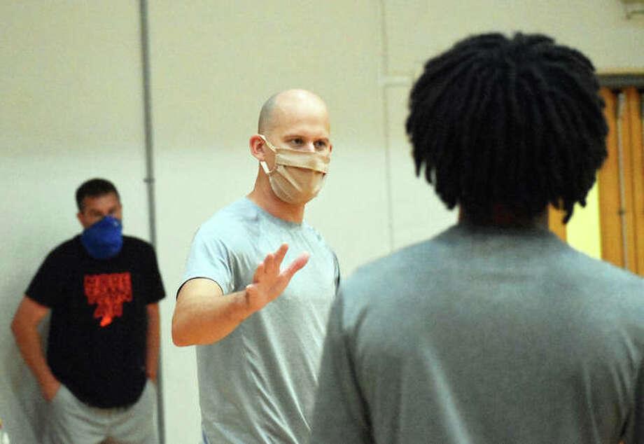 Edwardsville boys basketball coach Dustin Battas speaks to his team during a summer practice inside Lucco-Jackson Gymnasium.