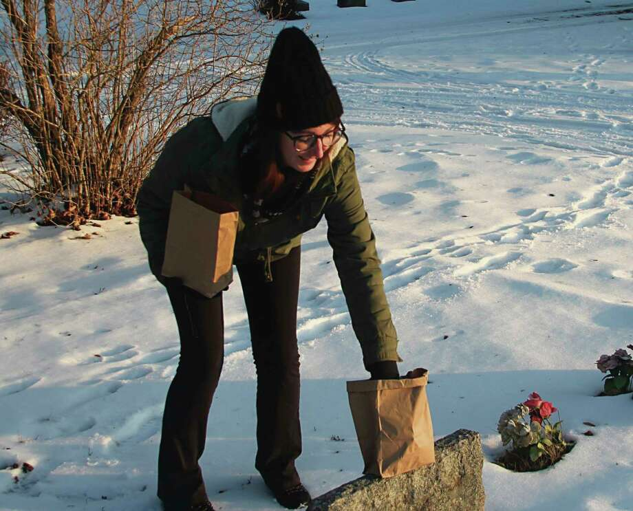 A volunteer places lighted luminaries on gravestones at Maple Grove Township cemetery. (File Photo)
