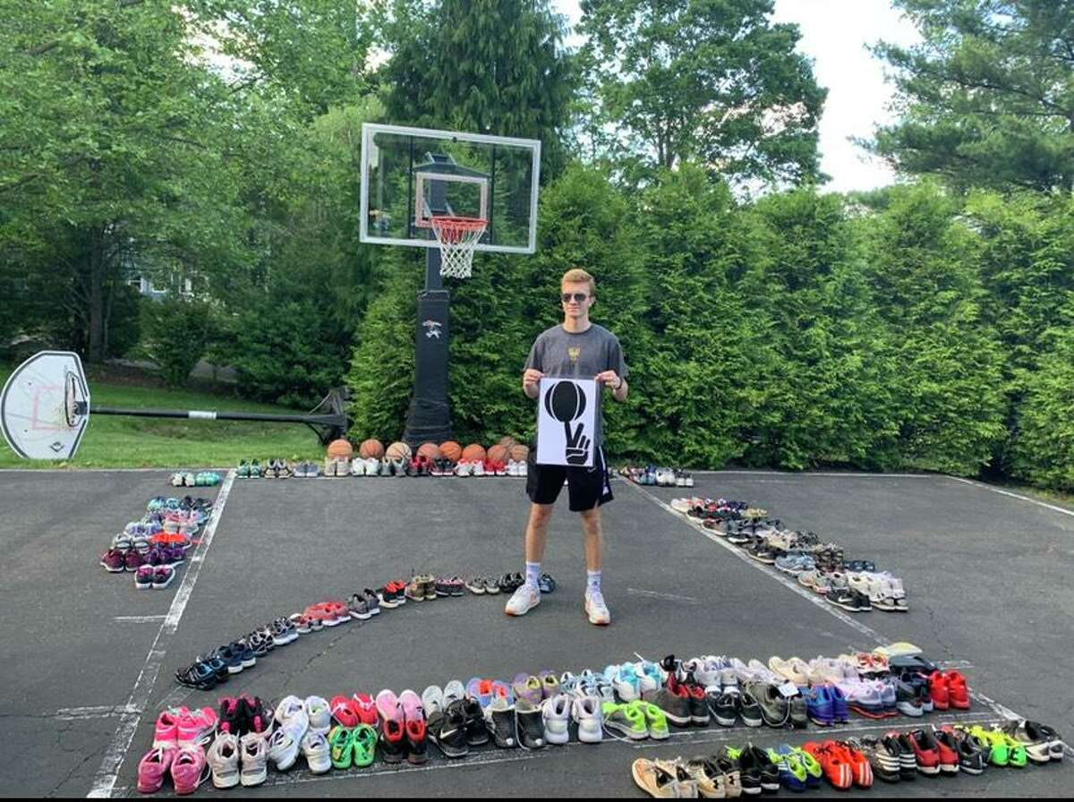 Trumbull's Lance Walsh standing with just a portion of the approximately 400 pairs of sneakers he was eventually able to donate to kids in need who live in inner-city communities.