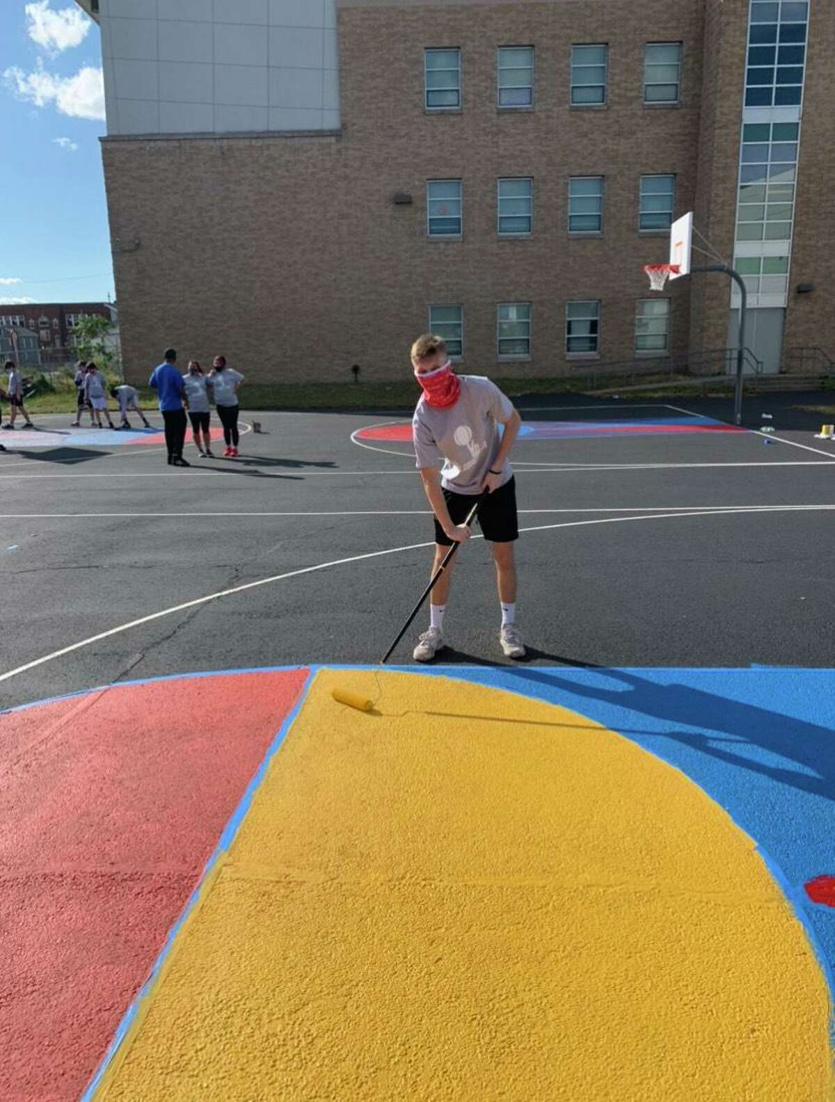 Trumbull's Lance Walsh paints a basketball court at The Barnum School in Bridgeport on Oct. 3, 2020.