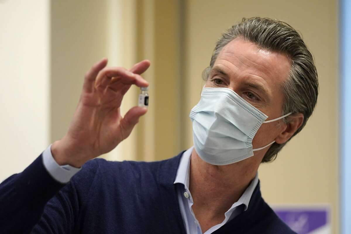 California Gov. Gavin Newsom holds up a vial of the Pfizer-BioNTech COVID-19 vaccine at Kaiser Permanente Los Angeles Medical Center in Los Angeles, Monday, Dec. 14, 2020.